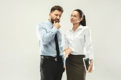 Angry boss. Man and his secretary standing at office or studio. Business men pointing to camera with his colleague. Female and male caucasian models. Office Royalty Free Stock Image