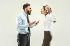 Angry boss. Man and his secretary standing at office or studio. Business men pointing to camera with his colleague. Female and male caucasian models. Office Stock Images
