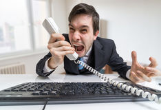 Angry boss or manager is calling and shouting to the telephone Royalty Free Stock Images