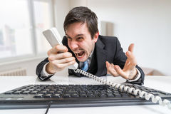 Angry boss or manager is calling and shouting to the telephone Stock Photos