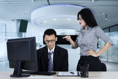 Angry boss pointing to her subordinate. Portrait of angry boss pointing to her subordinate while standing in the office Royalty Free Stock Images