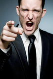 Angry boss points finger at employee and screams. Royalty Free Stock Photography