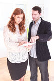 Angry boss and poor worker with heap of papers. Or notes at work indoors royalty free stock photography