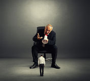 Angry boss screaming at small worker stock images