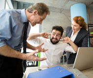 Angry boss screaming at workers. Mobbing, stress, work, scandal concepts. Angry bosses men and women screaming, shouting and yelling at their worker. Handsome Stock Photo