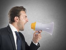 Angry boss shouting. Angry business boss shouting with his megaphone Stock Image