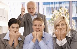 Angry boss shouting at scared employees. Angry boss shouting and pointing at scared employees in office Royalty Free Stock Images
