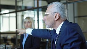Angry boss shouting at workers, showing loss charts, financial crisis, default. Stock footage stock video