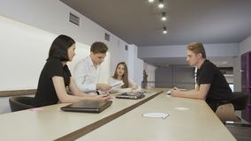 Angry boss throws the documents during working process. Young attractive people sit in the co-working space at the table. The leader of the team looks through stock footage