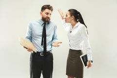 Angry boss. Woman and secretary standing at office or studio. Business men with his colleague. Female and male caucasian models. Office relationships concept Royalty Free Stock Photos
