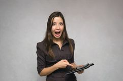 Angry boss woman with tablet pc. Angry business woman in a suit swears and screams at someone and pointing on the mobile tablet computer in her hands. Demanding royalty free stock photography