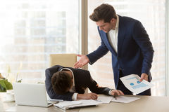 Angry boss yelling at depressed employee for failure, missed dea. Bad angry boss yelling at male sad depressed employee, lying with face down on office desk Royalty Free Stock Photos