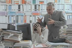 Angry boss yelling at his young employee. She is stressed and feeling frustrated: bullying boss and mobbing concept stock photography