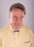Angry Bowtie Man. An angry looking man in a yellow shirt with a tiny blue bowtie Royalty Free Stock Images