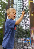 Angry boy. An angry young boy shouting through a chain link fence Stock Photography