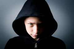 Angry boy. Boy with a sweatshirt and hood with glowing eyes Royalty Free Stock Photos