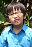Angry boy. Little boy in blue shirt showing angry face under the sun Royalty Free Stock Images