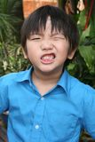 Angry boy. Little boy in blue shirt showing angry face in the park Royalty Free Stock Photography