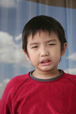 Angry boy. Little boy in red shirt showing angry face Royalty Free Stock Photo