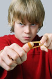 Angry Boy aiming a rubber band Stock Photos