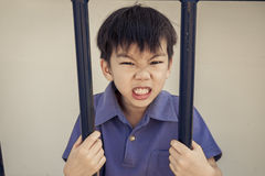 Angry boy behind a iron bar Royalty Free Stock Photography