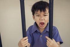 Angry boy behind a iron bar Royalty Free Stock Photo