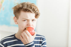 Angry boy biting into an apple. Close up on single angry teen boy in short hair and blue and white shirt biting into a red apple Stock Images