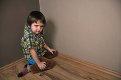 Angry boy in corner. Angry boy in kneeling corner Royalty Free Stock Images