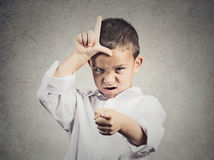 Angry boy displaying loser sign. Closeup portrait angry young Unhappy boy, young student displaying Loser Sign on forehead, pointing at you with disgust isolated royalty free stock photo