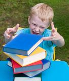 Angry boy doesn't like reading. Books Stock Photo