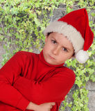 Angry boy dressed in red with christmas hat Stock Photos