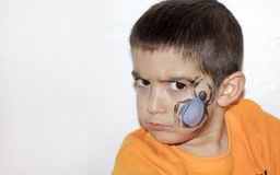 Angry boy with face painted with a spider Stock Photography