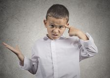 Angry boy gesturing with finger against temple are you crazy? royalty free stock photography