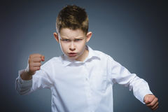 Angry boy isolated on gray background. He raised his fists to strike. Closeup Royalty Free Stock Photos
