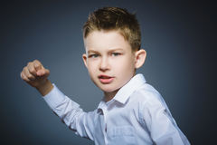 Angry boy isolated on gray background. He raised his fists to strike. Closeup Royalty Free Stock Photography