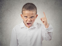 Angry boy screaming, demanding something. Closeup Portrait Angry child, Boy Screaming finger pointing up, demanding justice isolated grey wall background Stock Photography