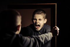 Angry Boy Shouting on his Own Mirror Reflection Royalty Free Stock Photo