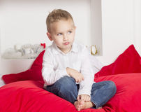 Angry boy sitting on a bed Royalty Free Stock Photo