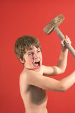 Angry boy swinging slede hamme. Picture of a boy swinging sledge hammer Royalty Free Stock Images