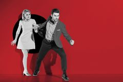 Angry boyfriend going with fashionable girlfriend. Through aperture on red royalty free stock photo