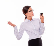 Angry brunette businesswoman with cell phone. Angry, frustrated businesswoman looking at cell phone while making a snuffy gesture with one hand and wearing her Royalty Free Stock Photos