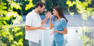 Composite image of angry brunette shouting at boyfriend. Angry brunette shouting at boyfriend against pretty house with a blue and white filter stock images