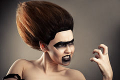 Angry brunette woman with dark makeup and lush hairdo. Closeup Stock Images