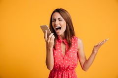 Angry brunette woman in dress screaming at smartphone. Over yellow background Stock Photos