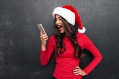 Angry brunette woman in red blouse and christmas hat screaming. On smartphone over black background Stock Image