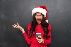 Angry brunette woman in red blouse and christmas hat screaming. And looking at smartphone over black background Stock Photography