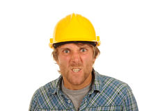 Angry builder in hard hat. Portrait of angry young builder in blue check shirt and hard hat; isolated on white background royalty free stock image