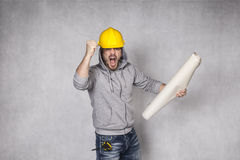 Angry builder holding blueprints in hand Stock Image