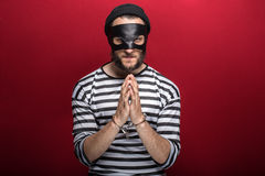 Angry burglar with handcuffs. Portrait on red background Royalty Free Stock Photo
