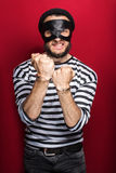 Angry burglar with handcuffs. Portrait on red background Royalty Free Stock Photography